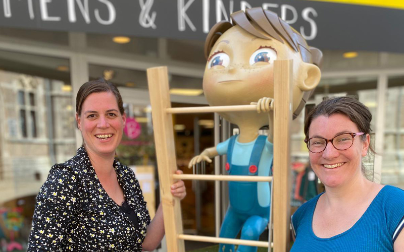 Jorien and Suzanne together with the 3D printed figure in front of their shop